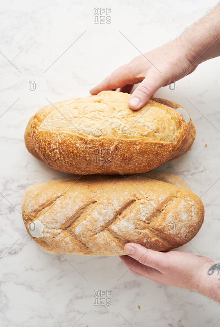 Top down view of baker's hands putting freshly baked bread onto a marble background