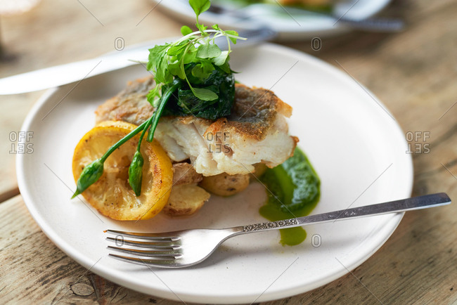 High angle view of portion of baked cod with watercress sauce and wild garlic