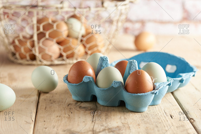 Fresh farm eggs in carton with basket in background