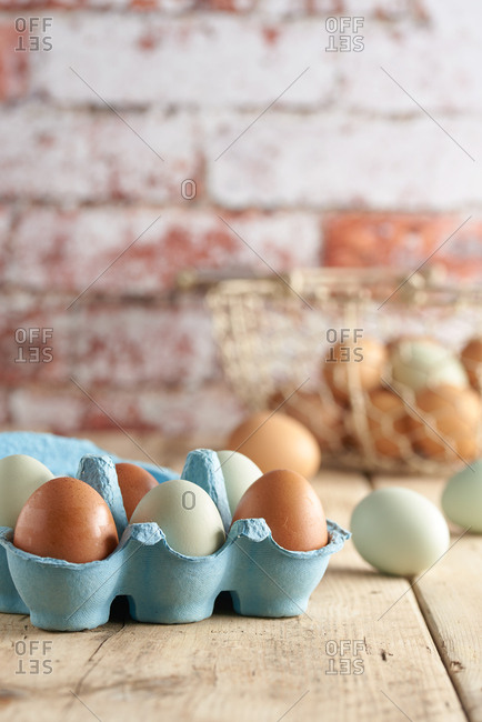 Free range organic farm eggs in carton and in basket in background