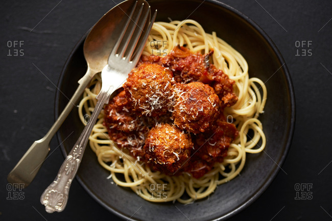 Top down view of homemade meatballs and spaghetti in dark bowl on dark background