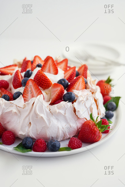 High angle view of pavlova dessert covered in summer berries