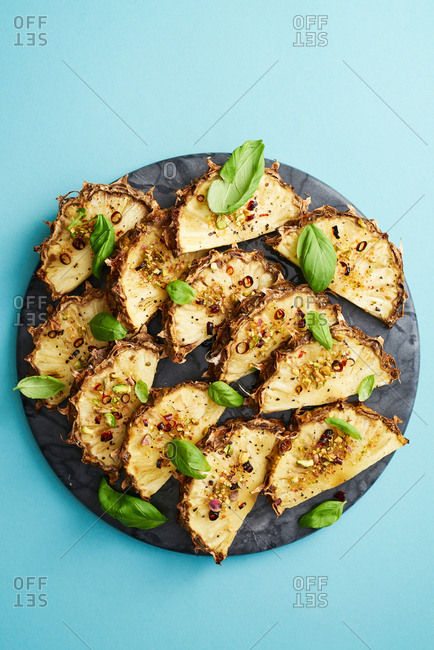 Flat lay of platter of roasted pineapple with basil, brown sugar, arbol chilies and pistachios on blue background