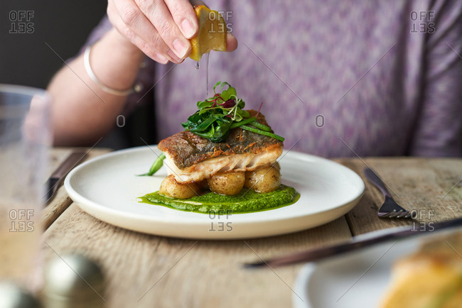 Detail of woman sitting at table squeezing lemon juice over baked cod with watercress sauce and wild garlic