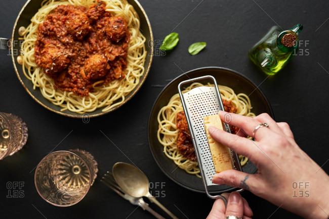 Top down view of woman grating fresh parmesan cheese on meatball and spaghetti pasta dish