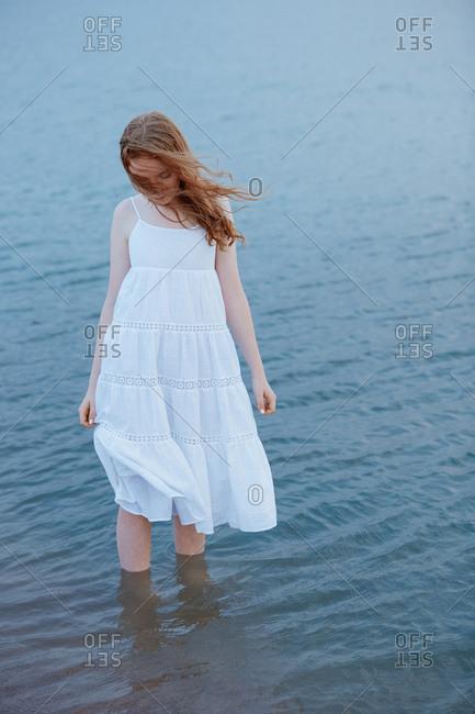 Redhead teenage girl walking in the sea