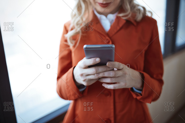 Woman in red coat using smartphone at office