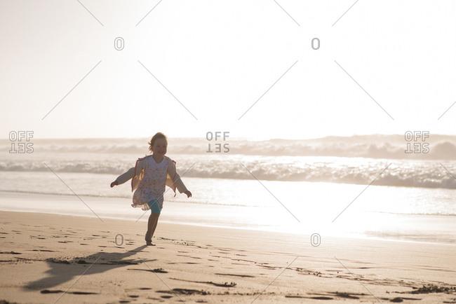 Laughing little girl running on the beach along the ocean