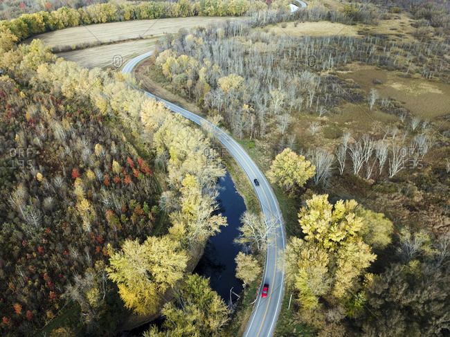 Cars driving past changing fall trees along Otter Creek and Route 73 in Brandon, Vermont
