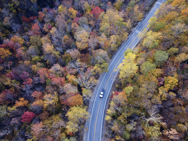 Drone view of car driving through scenic Route 73's fall foliage in Goshen, Vermont