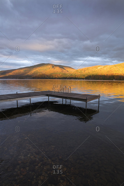 Shaded swimming dock on Vermont lake at sunset