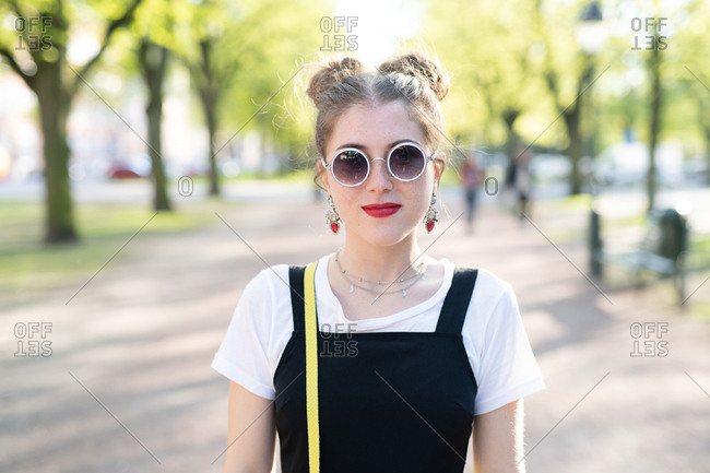 Female wearing round sunglasses and hair in buns