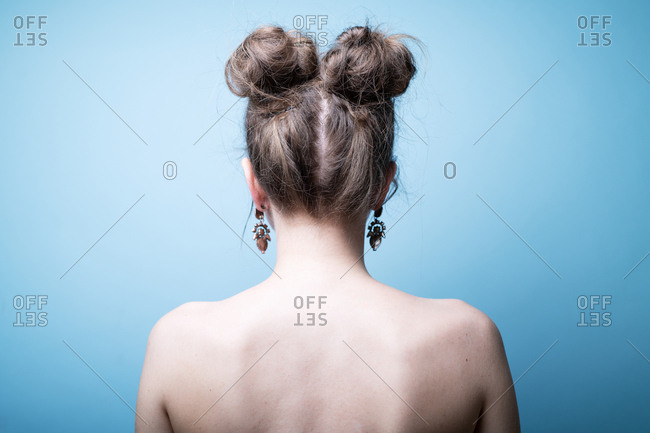 Rear view of female with pigtail hair buns against blue background