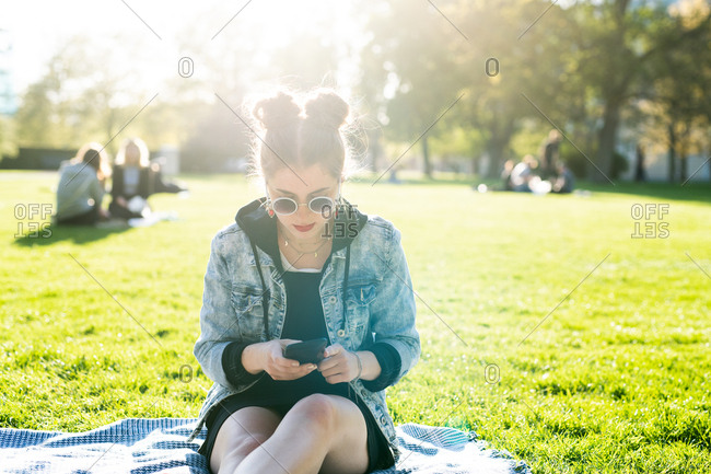 Female with pigtail hair buns sitting in a park