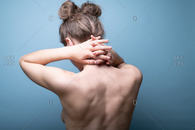 Female with pigtail hair buns putting hands behind neck on blue background