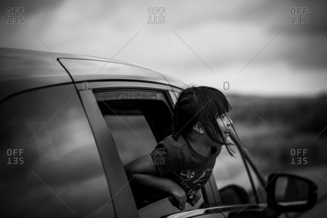 Portrait of a little girl looking out car window in black and white