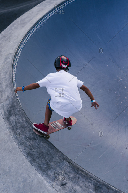 Canggu, Bali, Indonesia - March 19, 2018: Young man on edge of empty swimming pool while skateboard