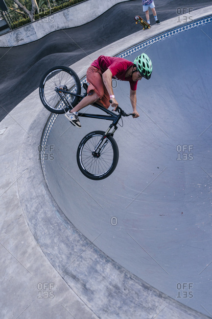 Canggu, Bali, Indonesia - March 19, 2018: Young man doing bike tricks in an empty pool at a skate park