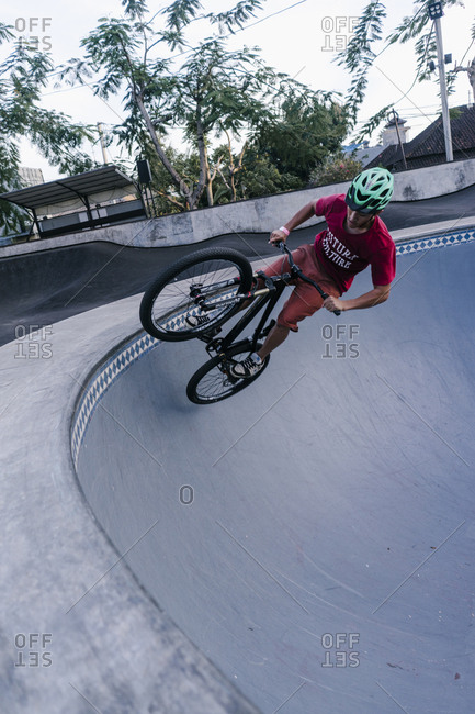 Canggu, Bali, Indonesia - March 19, 2018: Teen boy riding bike at a skate park