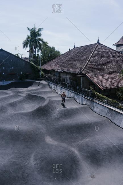 Canggu, Bali, Indonesia - March 19, 2018: Shirtless man riding on skateboard at a skate park