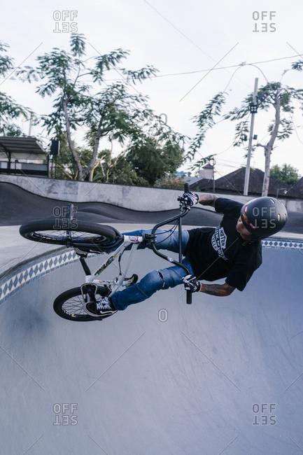 Canggu, Bali, Indonesia - March 19, 2018: Male doing bike tricks in an empty pool at a skate park