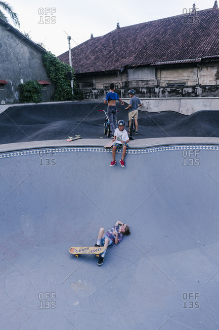 Canggu, Bali, Indonesia - March 19, 2018: Group of kids in an empty pool at a skate park