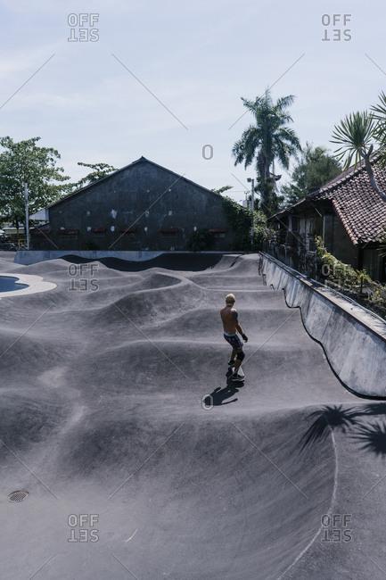 Canggu, Bali, Indonesia - March 19, 2018: Shirtless man skating at a skate park