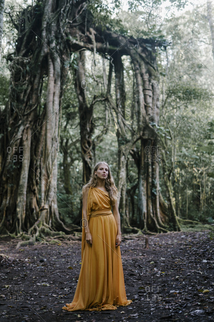 Blonde woman wearing golden gown by banyan trees