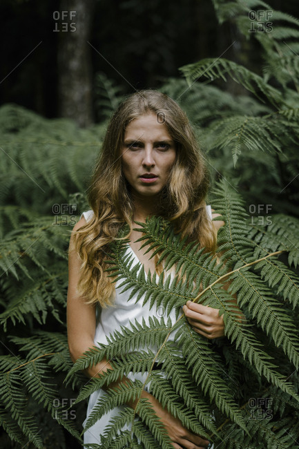 Blonde woman surrounded by fern plants