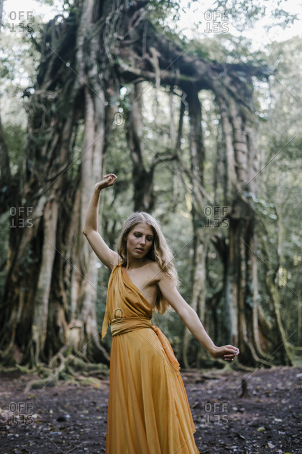 Woman wearing golden dress posing by banyan trees