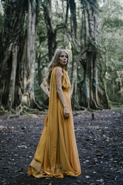 Blonde woman wearing golden dress in front of banyan trees