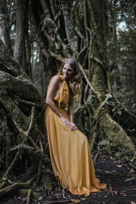 Blonde woman wearing golden dress leaning on a banyan tree