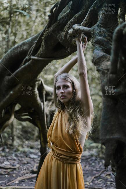 Woman wearing a yellow dress posing by a banyan tree