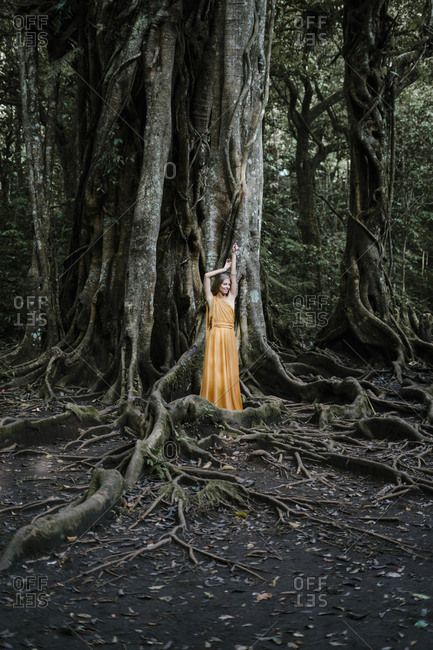 Woman wearing yellow dress posing by a banyan tree
