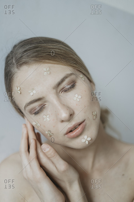 Woman with flower petals on her face