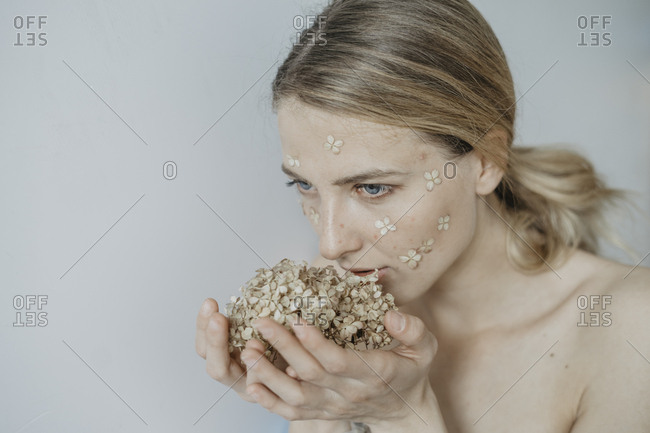 Woman with flower petals on her face smelling flowers