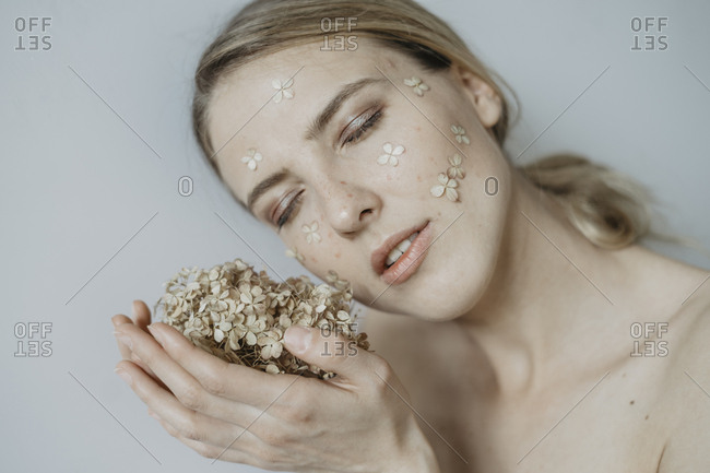 Woman with flower petals on her face holding flowers