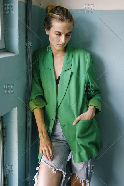Young woman with hand in pocket of her green blazer