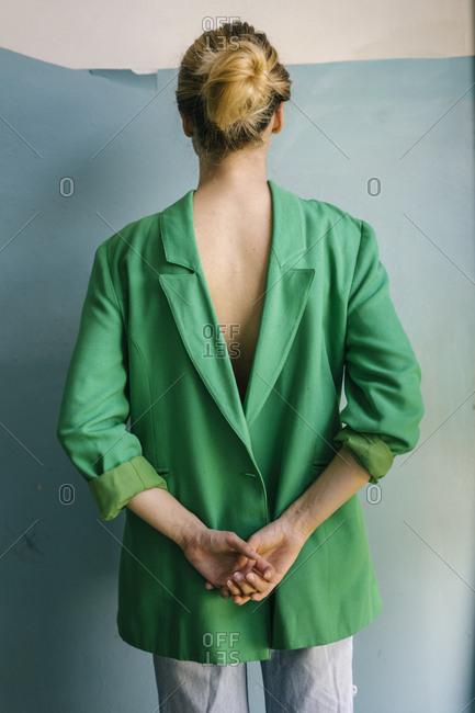 Young woman wearing green blazer backwards