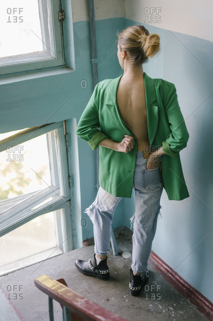 Rear view of woman with hand in pocket wearing green blazer