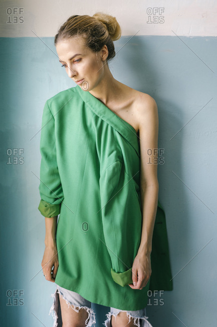 f97b4a10eec8 Woman wearing green blazer on one shoulder stock photo - OFFSET