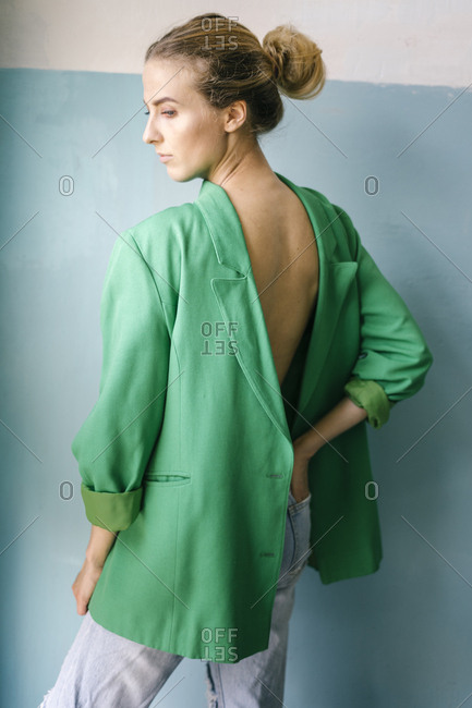 Profile view of woman with hand in pocket wearing green blazer