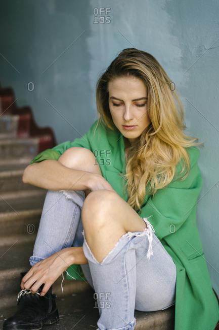 Blonde woman on steps wearing green blazer