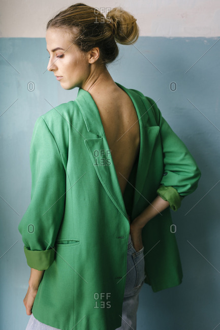Blonde woman with hand in pocket wearing green blazer