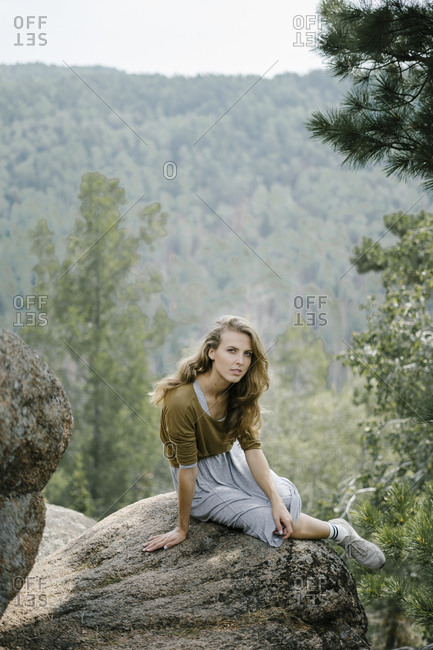 Blonde woman sitting on rocky mountain ledge