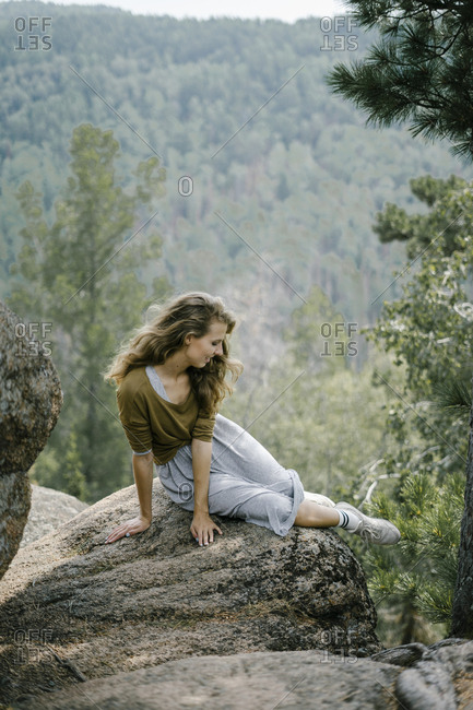 Young woman sitting on rocky mountain ledge looking away