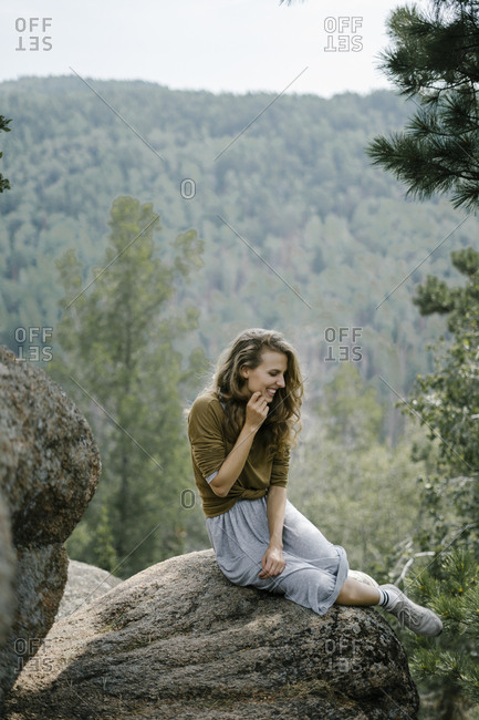 Happy woman sitting on rocky mountain ledge