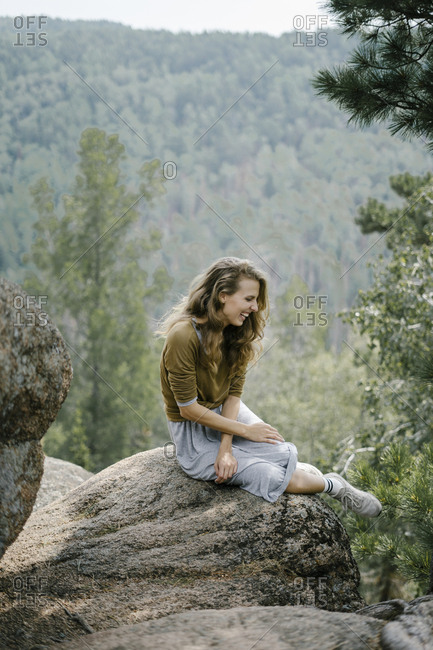 Laughing woman sitting on rocky mountain ledge