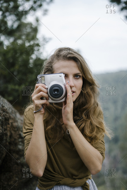 Woman holding camera in rural mountain setting