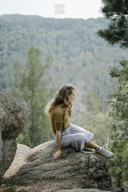 Woman sitting on rocky mountain ledge